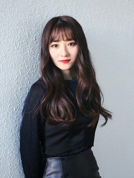 SuA from band Dreamcatcher smiling into the camera against grey wall